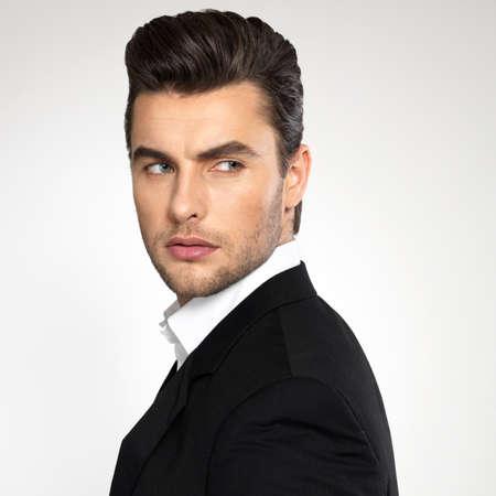 viso uomo: Primo piano volto di una moda giovane uomo d'affari in abito nero casuale pose in studio Archivio Fotografico