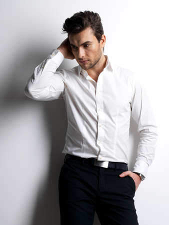 enticement: Fashion portrait of young man in white shirt poses over wall with contrast shadows
