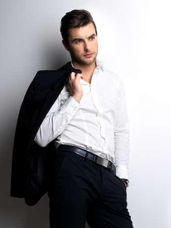uomini belli: Moda giovane uomo in camicia bianca detiene la giacca nera sulla parete con le ombre di contrasto Archivio Fotografico