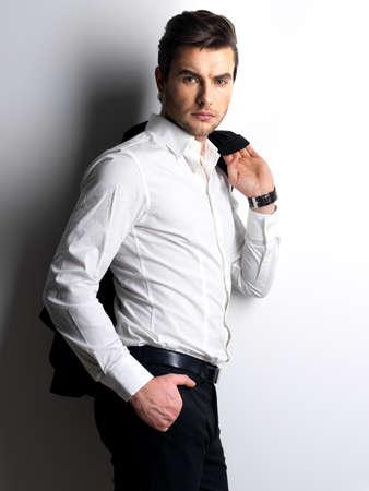 moda ropa: Forme el retrato del hombre joven en camisa blanca posa sobre la pared con las sombras de contraste Foto de archivo