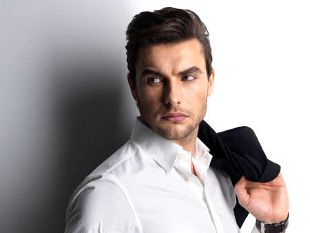 enticement: Fashion young man in white shirt holds the black jacket  over wall with contrast shadows