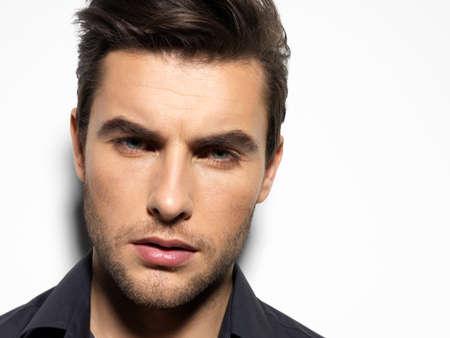 visage homme: Mode portrait de jeune homme en chemise noire pose sur mur avec ombre contraste