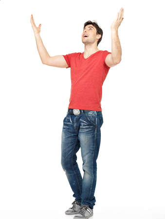 people looking up: Young happy man in casuals with raised hands up isolated on white background. Stock Photo