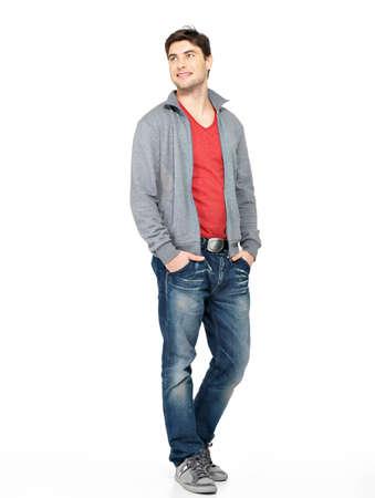 Volledige portret van lachende gelukkig knappe man in grijze jas, blauwe spijkerbroek. Mooie jongen staande op een witte achtergrond loking weg