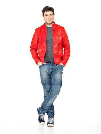 Full portrait of smiling happy handsome man in red jacket, blue jeans and gymshoes. Beautiful guy standing  isolated on white background  photo