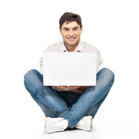 casuals: Portrait of  happy man working on laptop  in casuals - isolated on white. Concept communication.