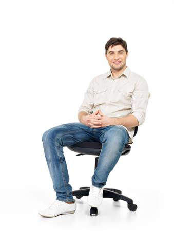 persona sentada: Retrato de hombre sonriente feliz se sienta en la silla de la oficina aislada en blanco. Foto de archivo