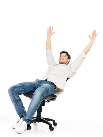 Portrait of smiling happy man sits on the chair and raised hands up isolated on white.