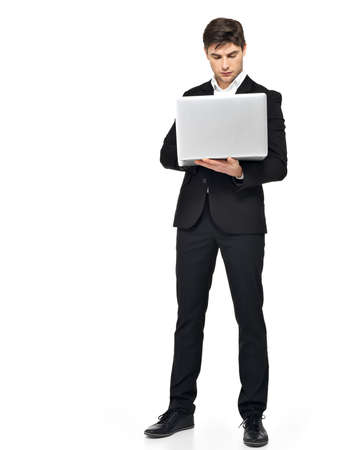 standing man: Full portrait of businessman working on laptop  isolated on white. Concept communication.