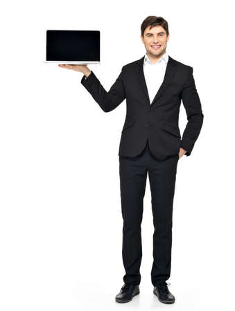 Portrait of  businessman holds on palm the opened  laptop with blank black screen isolated on white.   photo