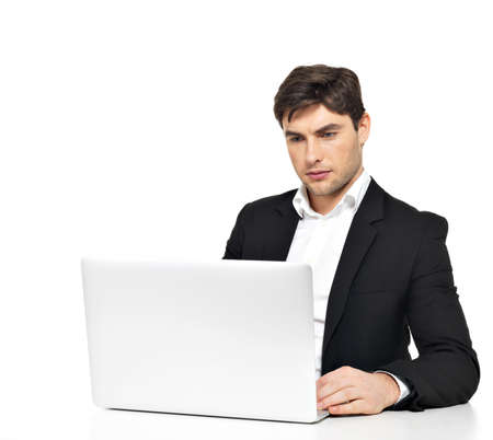 Portrait of thinking young office worker with  laptop sitting on the table  isolated on white. photo
