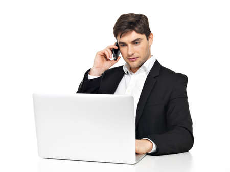 speaks: Portrait of young office worker with  laptop speaks by mobile phone sitting on the table  isolated on white.