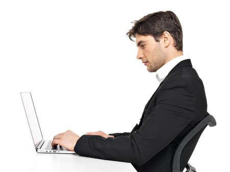 business man laptop: Retrato del pensamiento joven empleado de oficina con ordenador port�til sentado en la mesa aislada en blanco.