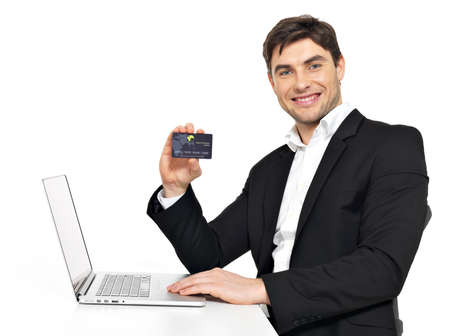 Portrait of office worker with  laptop and credit card sitting on the table  isolated on white. photo