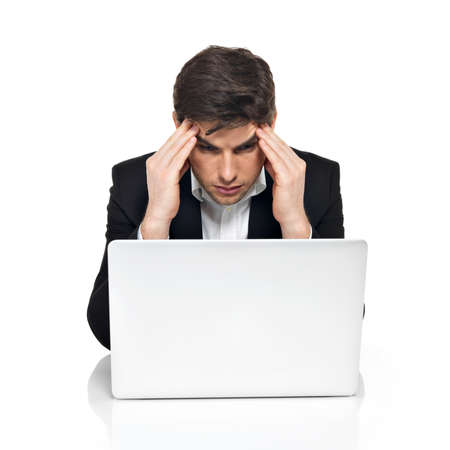 Portrait of thinking office worker with laptop having stress sitting on the table,  isolated on white. photo