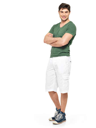 casual clothing: Full portrait of smiling happy handsome man in white shorts and green t-shirt - isolated on white background