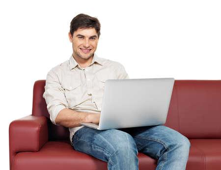 divan: Portr�t gl�cklich l�chelnde Mann mit Laptop sitzt auf dem Sofa, isoliert auf wei�. Lizenzfreie Bilder