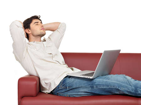 divan: Portrait of resting man with laptop sits on the divan, isolated on white.   Stock Photo