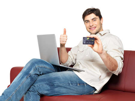 Portrait of smiling happy man with laptop gives the thumbs up and shows the credit card isolated on white.   photo