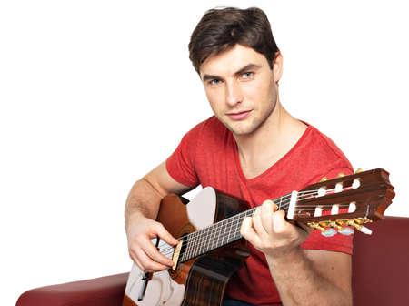 divan: Sonriendo guitarrista toca en el isolatade ac�stico guitat sobre fondo blanco. Hombre joven hermoso que se sienta con la guitarra en el div�n
