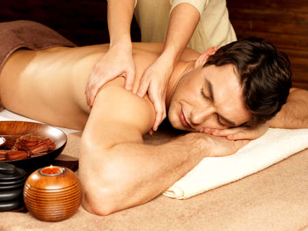 and the horizontal man: Masseur doing massage on man body in the spa salon. Beauty treatment concept. Stock Photo
