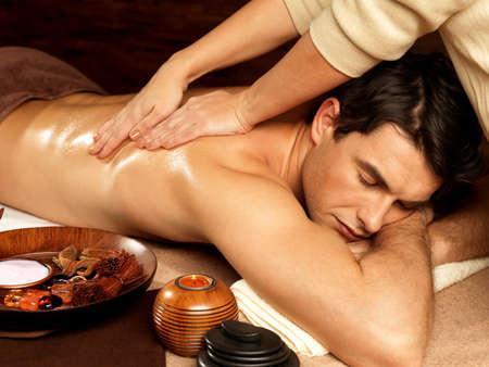 masoterapia: Masajista haciendo masaje en el cuerpo del hombre en el salón de spa. Belleza concepto de tratamiento.