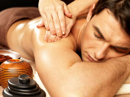 massage homme: Masseur faisant le massage sur le corps de l'homme dans le salon de spa. Beauté concept de traitement.