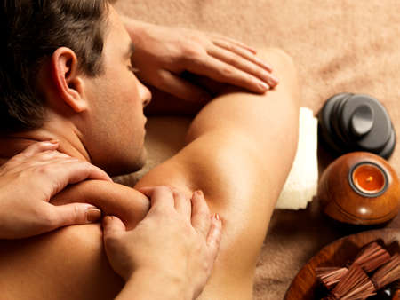 male massage: Masseur doing massage on man body in the spa salon. Beauty treatment concept. Stock Photo