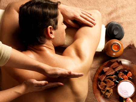 candles spa: Masseur doing massage on man body in the spa salon. Beauty treatment concept. Stock Photo