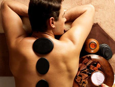 calm down: Handsome man having stone massage in spa salon. Healthy lifestyle.