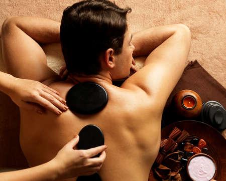 massage stones: Handsome man having stone massage in spa salon. Healthy lifestyle.