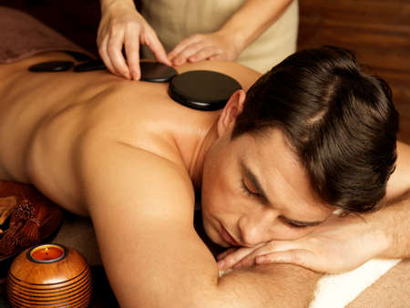man lying down: Handsome man having stone massage in spa salon. Healthy lifestyle.