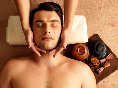 pamper: Masseur doing head massage on man in the spa salon.