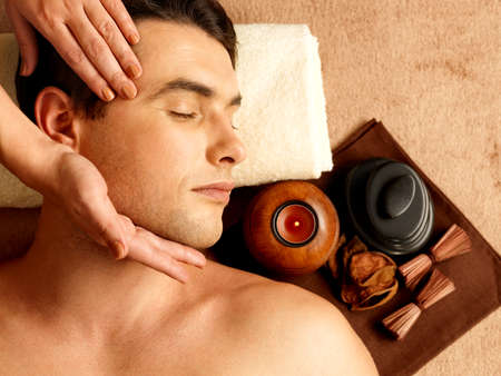 massage hands: Masseur doing head massage of temples on man in the spa salon.  Stock Photo