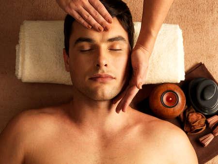 masoterapia: Masajista haciendo masaje en la cabeza del hombre en el salón de spa.