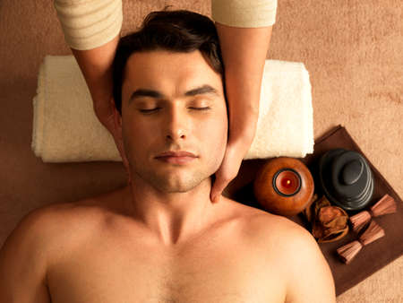 Masseur doing neck massage on man in the spa salon.  photo