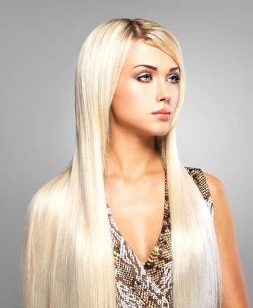 Beautiful woman with long straight blond hair. Fashion model posing at studio. photo
