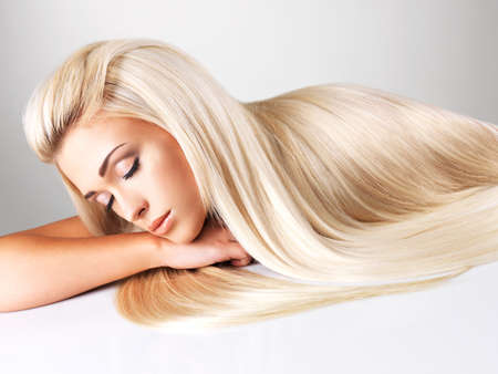 beautiful hair: Beautiful woman with long straight blond hair. Fashion model posing at studio.