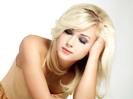 Portrait of the beautiful blond woman with style hairstyle poses on grey background photo
