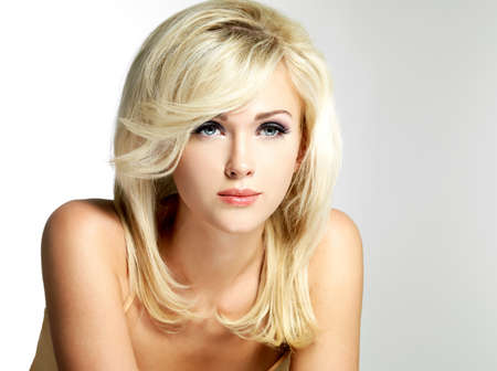 Beautiful blond woman with style hairstyle poses at studio photo