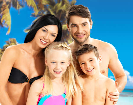 Portrait of  happy smiling beautiful family with two children at tropical beach photo