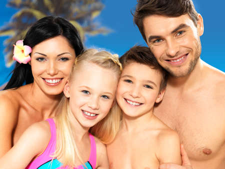 Retrato de familia feliz sonriendo hermosa con dos ni�os en la playa tropical photo