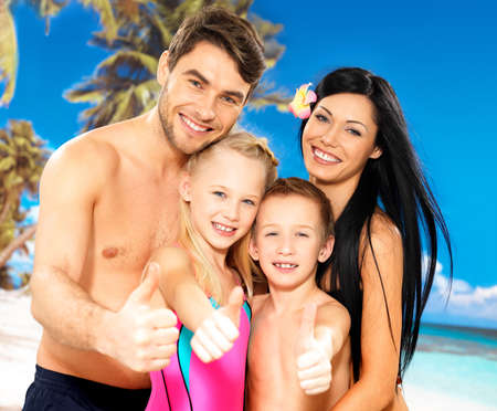 Portrait of  happy smiling family with thumbs up sign  at tropical beach photo