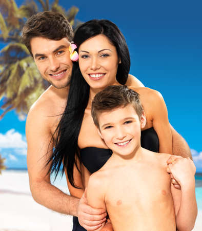 Portrait of  happy smiling beautiful family with child at tropical beach photo