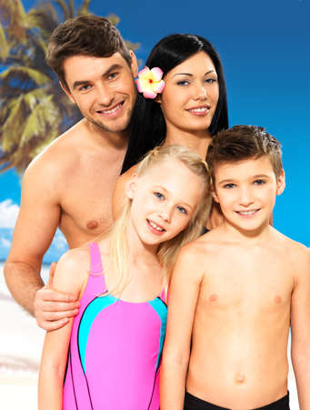 offspring: Portrait of  happy smiling beautiful family with two children at tropical beach