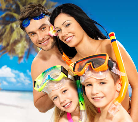 Portrait of  happy fun beautiful family with two children at tropical beach with protective swimming mask photo