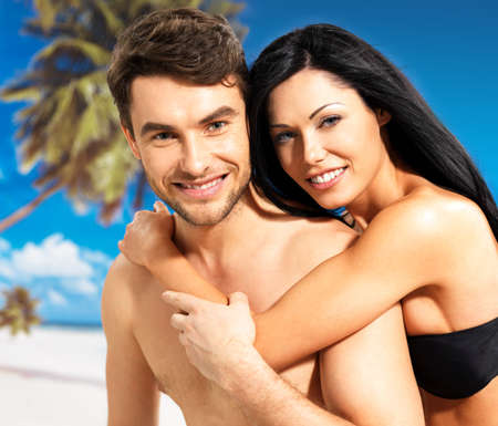 tanned: Portrait of  happy smiling beautiful couple in love  at tropical beach