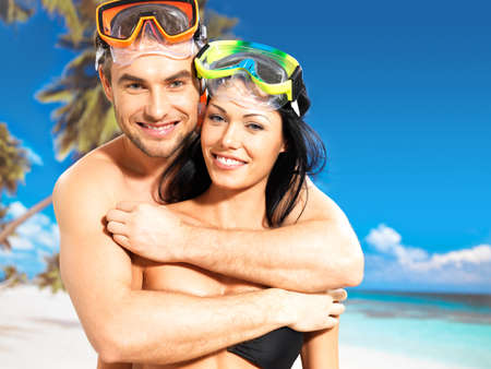Portrait of  happy fun beautiful couple  at tropical beach with swimming mask on face photo