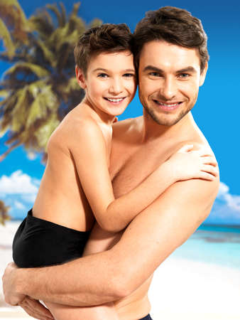 Portrait of  happy smiling father hugs son 8 years old at tropical beach photo