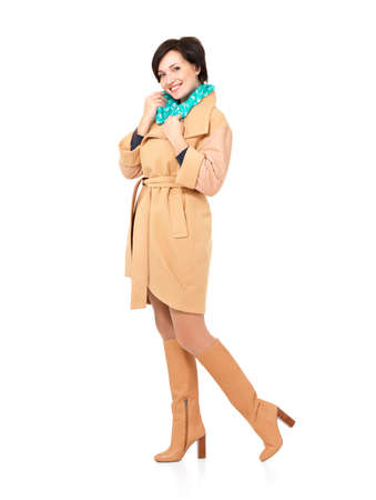 women in boots: Full portrait of happy woman in fall coat leather boot with green scarf standing isolated on white background